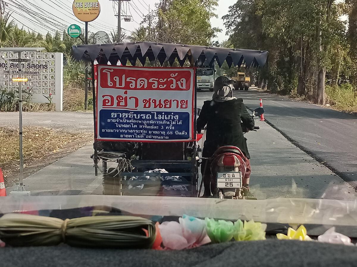 คุณยายขับรถจักรยานยนต์พ่วงข้าง พร้อมป้ายข้อความ โปรดระวังอย่าชนยาย